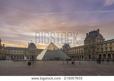 PARIS, FRANCE - DECEMBER 12, 2017: View of famous Louvre Museum with Louvre Pyramid at evening. Louvre Museum is one of the largest and most visited museums worldwide