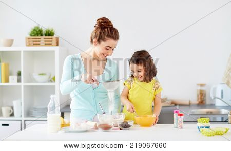 family, cooking, baking and people concept - happy mother and little daughter with sieve sifting flour and making dough at home kitchen