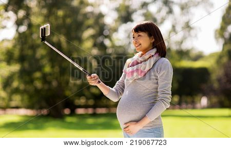 pregnancy, people and technology concept - happy pregnant asian woman with smartphone selfie stick taking picture at park