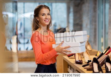 sale, shopping and people concept - happy young woman or shop assistant with shoe boxes at store