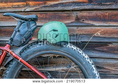 fat bike wheel , saddle and  helmet against rustic wooden cabin wall