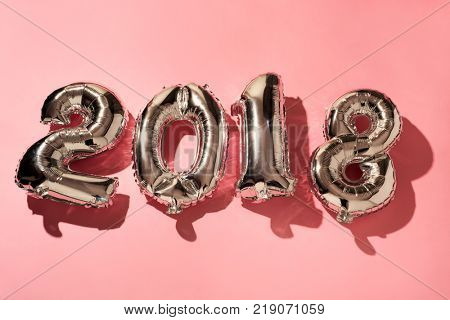 some silvery number-shaped balloons forming the number 2018, as the new year, against a pink background
