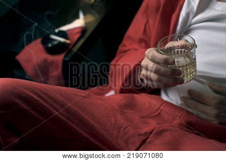 closeup of a young man wearing a santa suit drinking whisky and smoking a cigarette in bed