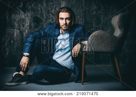 Vogue shot of a handsome man sitting near the armchair at studio. Furniture and interior. Male beauty, fashion.