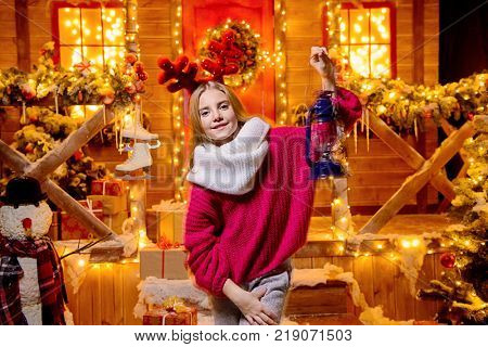 Pretty child girl is standing on the porch of a house decorated for Christmas and holding a lantern. Time for miracles.