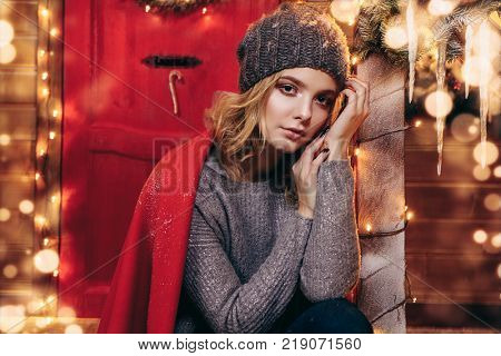 Pretty girl in a knitted sweater and hat is sitting on the porch of a house decorated for Christmas . Time for miracles.