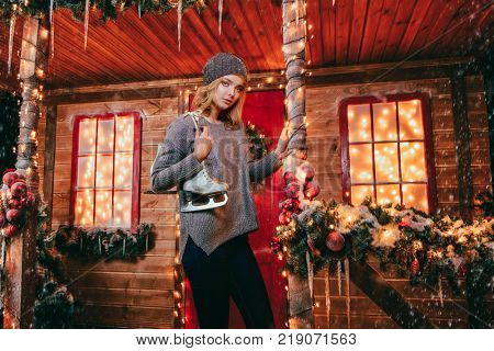 Happy girl in a warm winter clothes and skates in her hands, stands near the house decorated for Christmas. Time for miracles. Merry Christmas and Happy New Year.