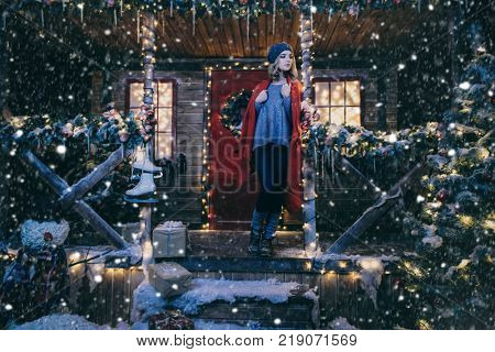 Happy girl in a warm winter clothes and blanket poses near the house decorated for Christmas. Time for miracles. Merry Christmas and Happy New Year.