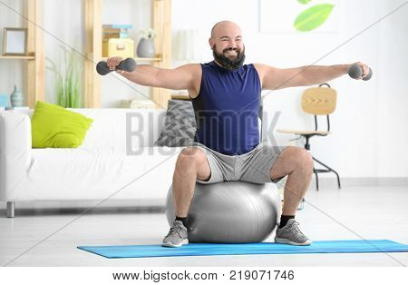 Overweight man doing exercises at home