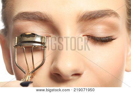 Woman using eyelash curler, closeup
