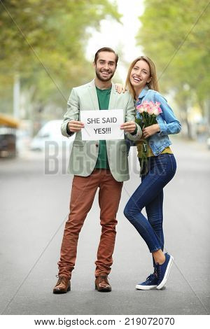 Young man holding paper with text SHE SAID YES and his happy beloved on engagement day outdoors