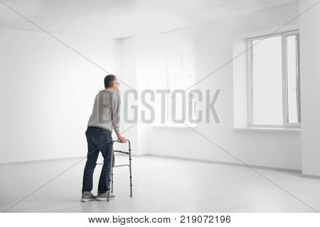 Senior man with walking frame in empty room