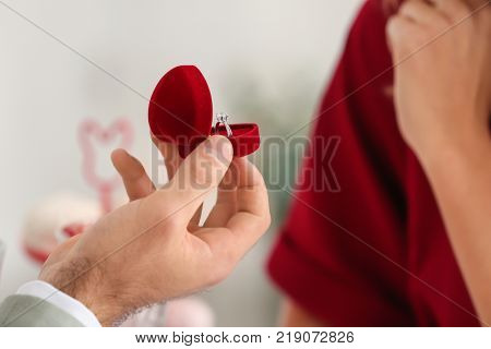 Young man with engagement ring making proposal to his beloved girlfriend in restaurant, closeup