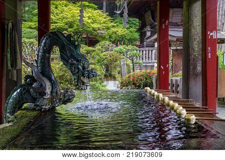 Fujiyoshida city- Japan, June 13, 2017: Purification basin with a water dragon at Fujiyoshida Sengen Shrine in Fujiyoshida city