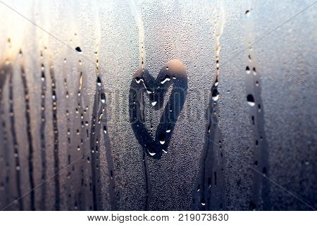 A rainy winter day seen through a wet window a moment before sunset.
