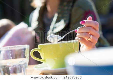 Woman spooning froth on a cappuccino as she sits outdoors in the sunshine holding a baby girl on her lap.