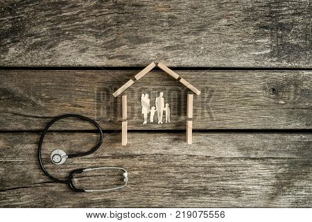 Cut outs of a young family with kids in a house with a stethoscope lying on a rustic wood background alongside in a conceptual image.