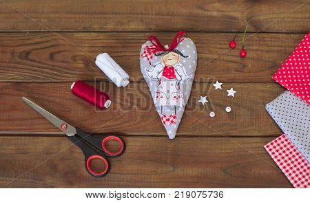 Making of textile handmade christmas toys on wooden background. Making xmas tree decoration or greeting card. Cut the toy. Easy Christmas crafts.