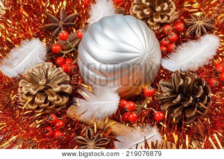 Pines cones cinnamon sticks star anise feather and silvery bauble on an orange tinsel as decoration for Christmas
