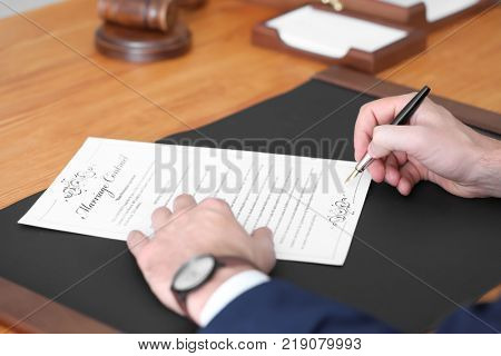 Male notary signing marriage contract, closeup