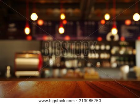 top of wood table with blur counter of coffee shop or cafe bar with orange lamp light background