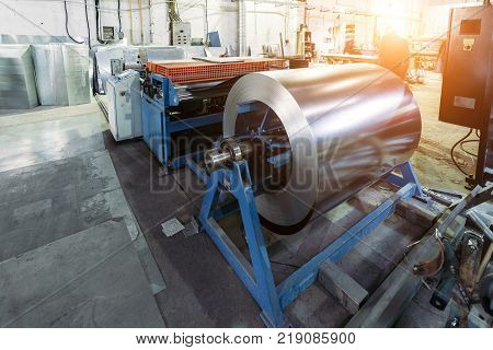 Metalworking factory. Roll of galvanized steel sheet for manufacturing metal pipes and tubes in the factory.