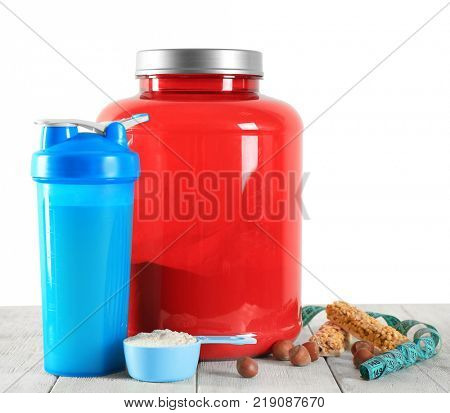 Protein shake in bottle, powder, bars and measuring tape on table