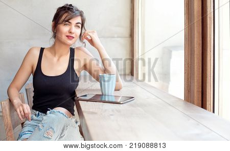 Beautiful brunette woman thinking and daydreaming about future plans or memories while sitting down during coffee break indoors