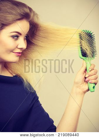 Woman brushing her long blonde hair using brush morning beauty routine. Haircare and hairstyling concept. poster