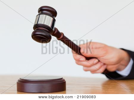 Hand knocking a gavel against a white background