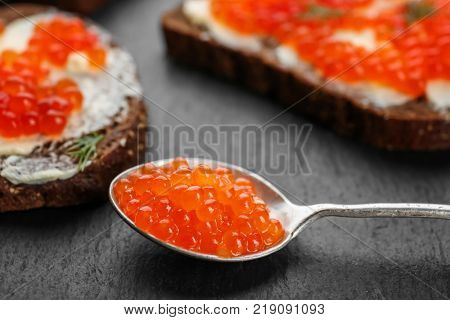 Spoon with delicious red caviar on table, closeup