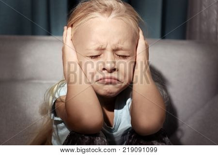 Helpless little girl covering her ears indoors. Child abuse concept