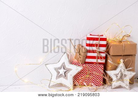 Colorful wrapped gift boxes with presents fairy lights and decorative stars on white textured background. Selective focus. Place for text.