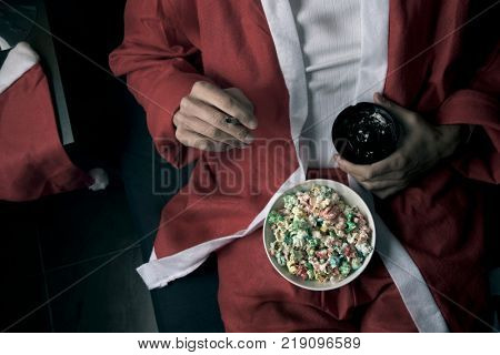 closeup of a young man wearing a santa suit smoking a cigarette and eating pop corn in bed