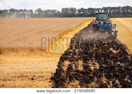 Tractor preparing land for sowing. Farmer in tractor preparing land with seedbed cultivator