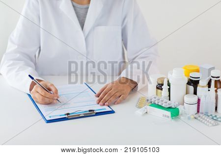 medicine, healthcare and people concept - doctor with drugs and clipboard writing prescription or medical report at hospital