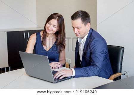 Business man explaining something to a woman with a laptop in an office.
