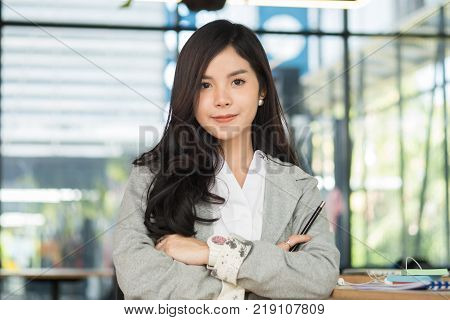 confident businesswoman sitting with arms crossed at office. successful young female entrepreneur woman smiling at workplace. working, business concept