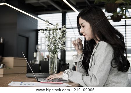 Woman Holding A Credit Card And Using Laptop Computer For Online Shopping At Cafe. Businesswoman Pur
