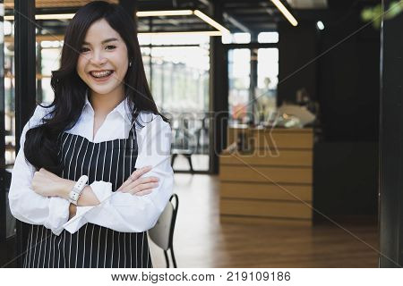 small business owner standing with arms crossed at coffee shop. asian female barista wearing apron smiling at cafe. food service, restaurant concept.
