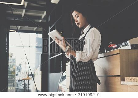 small business owner holding tablet at counter in coffee shop. asian female barista wearing apron using touchpad at bar in cafe. food service, restaurant, entrepreneur concept.