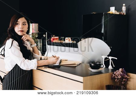 small business owner with notebook at counter in coffee shop. asian female barista wearing apron writing note at bar in cafe. food service, restaurant, entrepreneur concept.