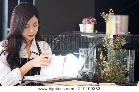 small business owner with notebook at counter in coffee shop. asian female barista wearing apron at bar in cafe. food service, restaurant, entrepreneur concept.