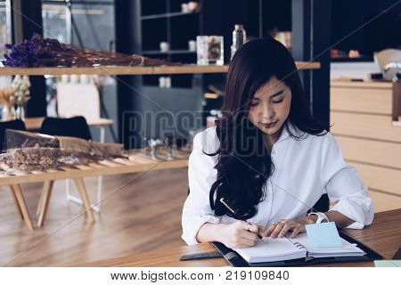 asian businesswoman write note on notebook at workplace. startup woman working with business plan report document at office.  young female entrepreneur analyze accounting market data.  financial adviser with paperwork on table.