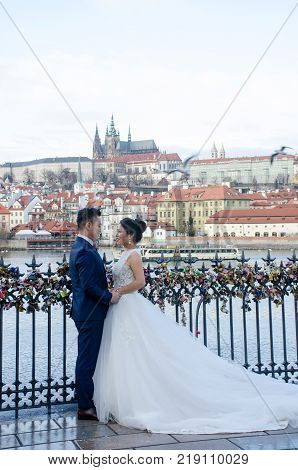 Prague Czech Republic -5 December 2017: Oriental Couple getting married at Charles Bridge Prague with St Vitus Cathedral in background