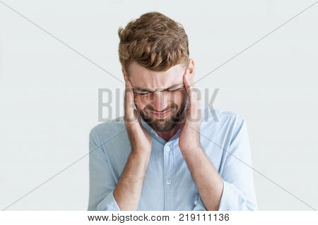 Closeup portrait of frustrated handsome young man touching aching head. Businessman feeling high stress and headache. Stressful job and work balance concept