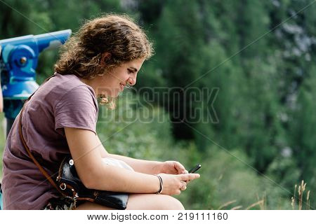 Portrait of young woman smiling and sitting in viewpoint in the mountain texting on smartphone against landscape. Alps, Austria