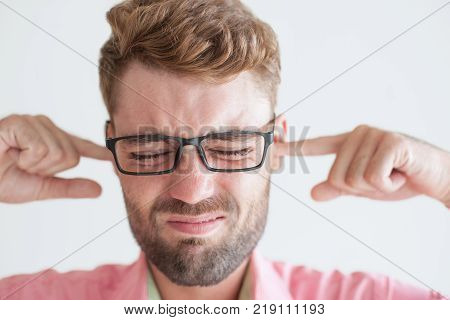 Closeup portrait of annoyed handsome young man stopping his ears with fingers. Businessman getting too much news and feeling high stress. Stressful job and stopping ears concept