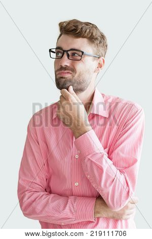 Portrait of sceptic handsome young man wearing glasses and keeping hand on chin. Businessman pondering deal. Doubts at business concept