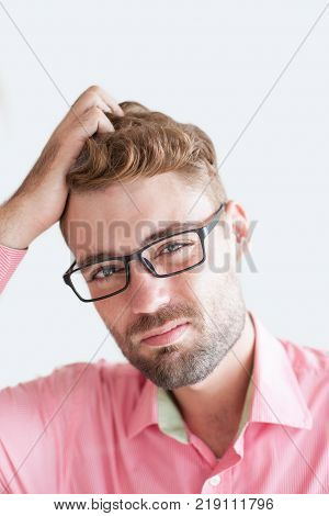 Portrait of suspicious handsome young man wearing glasses and scratching his head. Businessman doubtful of project. Doubts at business concept